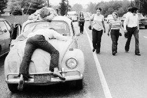 Two festival goers that found Woodstock too much lay passed out on a car bonnet. Picture: Getty Images