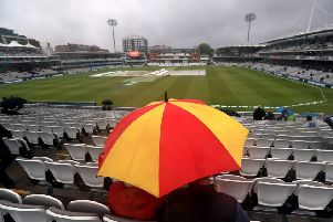Fans shelter from the rain at Lord's.