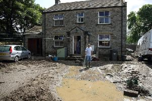 A man surveys the remains of his front garden in Reeth after flash floods destroyed it