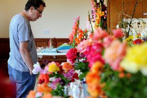 The annual Cockerham Village Show in the village hall  featured classes for flowers, vegetables, photography, handicrafts, cookery, art and floral art. A visitor admires some of the blooms. Picture by Paul Heyes, Saturday August 10, 2019.