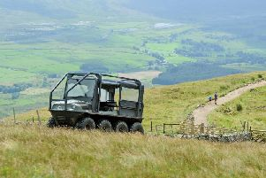 A ranger drives an ATV to the summit of Whernside