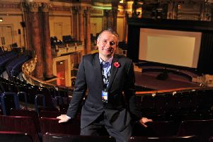 Leeds International Film Festival director Chris Fell in front of a huge movie screen within the impressive setting of Leeds Town Hall. Picture by Tony Johnson.