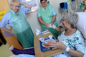 Prime Minister Boris Johnson serves food to Wenona Pappin, 70, during a visit to Torbay Hospital in Devon after he welcomed a review into hospital food following the deaths of six people due to a listeria outbreak. PRESS ASSOCIATION Photo. Picture date: Friday August 23, 2019. Great British Bake Off judge Prue Leith is to advise a Government review into hospital food launched by the Department of Health and Social Care on Friday, which will examine whether the number of hospitals catering in-house can be increased.